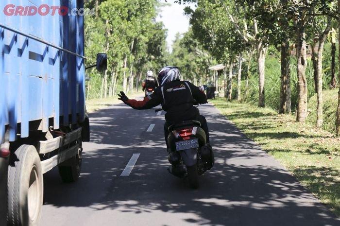 Ilustrasi rider NMAX tengah mendahului sebuah truk