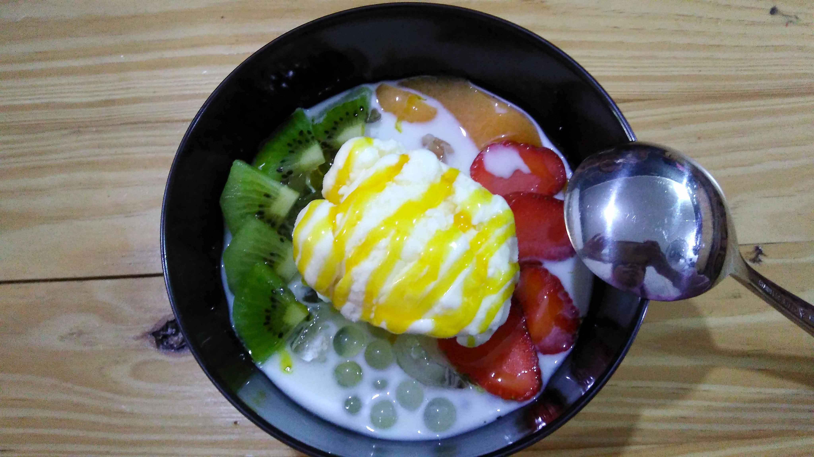 Dessert Tropicana Tuti Fruty dengan topping pudding mangga, popping boba, jelly plain, kiwi, stroberi, es krim dan mango sauce.